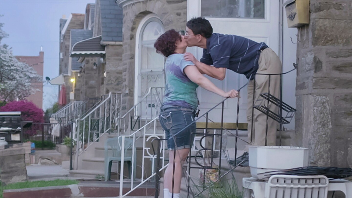 """Dina and her partner Scott exchange a kiss on a doorstep. 