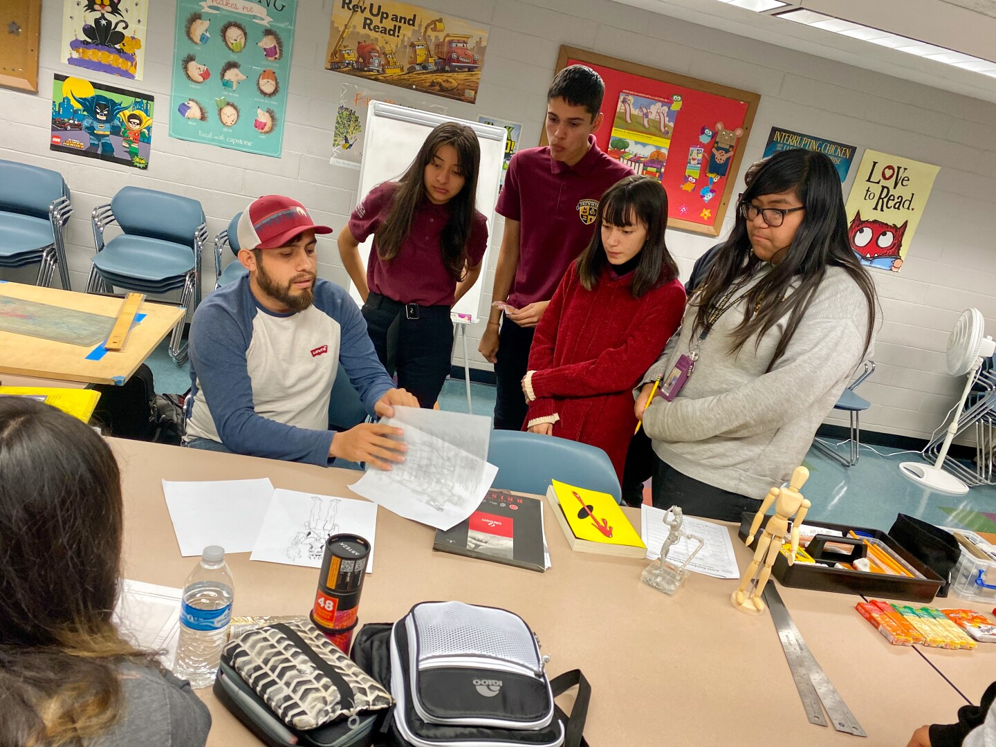 Artist Abraham Jarmillo guides a workshop about comic book coloring at a table in the Vernon - Leon H. Washington Jr. Memorial Branch Library. Students gather around him.