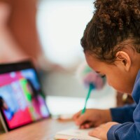 A little girl attends classes remotely | iStock