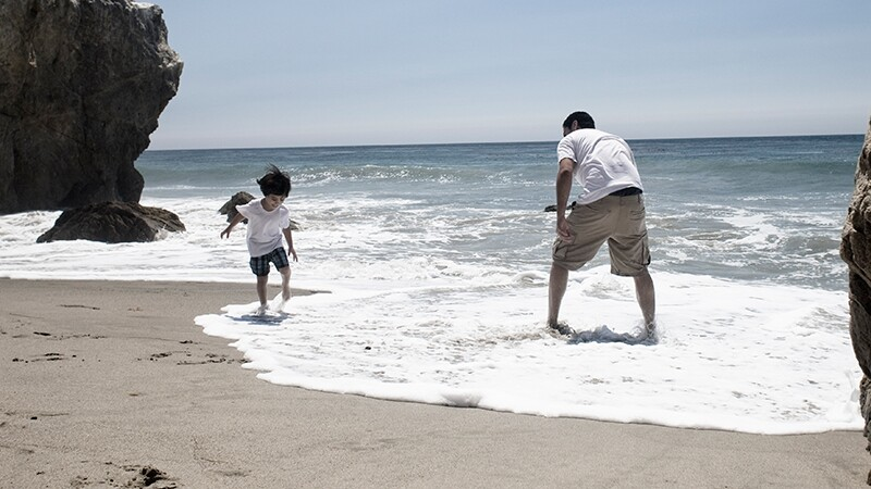 Latino family members play on the beach at Malibu | Photo: depphoto/iStockPhoto