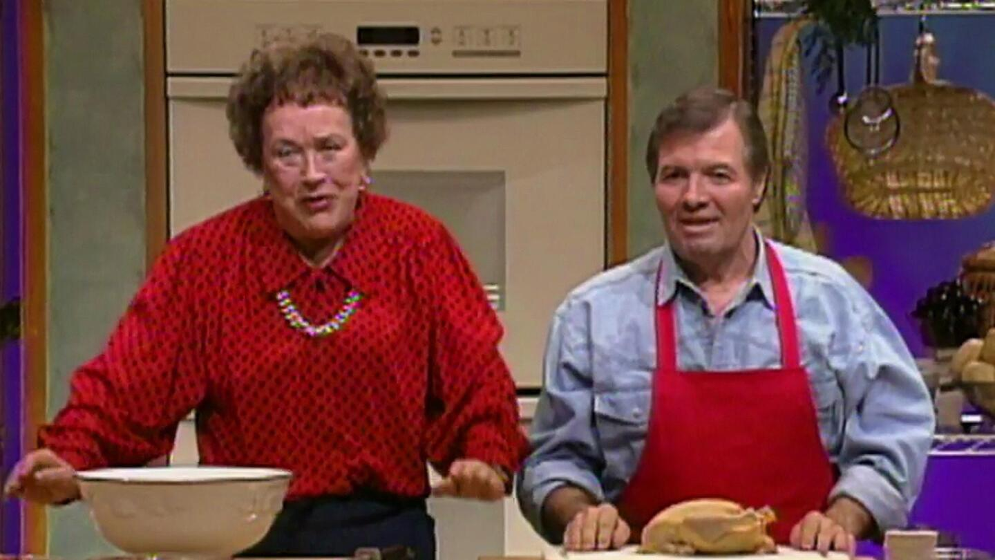 Julia Child and Jacques Pepin stand beside each other at a kitchen set.