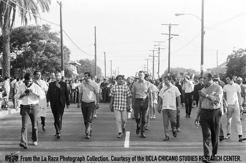 CSRC_LaRaza_B4F3C1_Staff_016 Father Luce and others lead protesters during the National Chicano Moratorium in Laguna Park | La Raza photograph collection. Courtesy of UCLA Chicano Studies Research Center