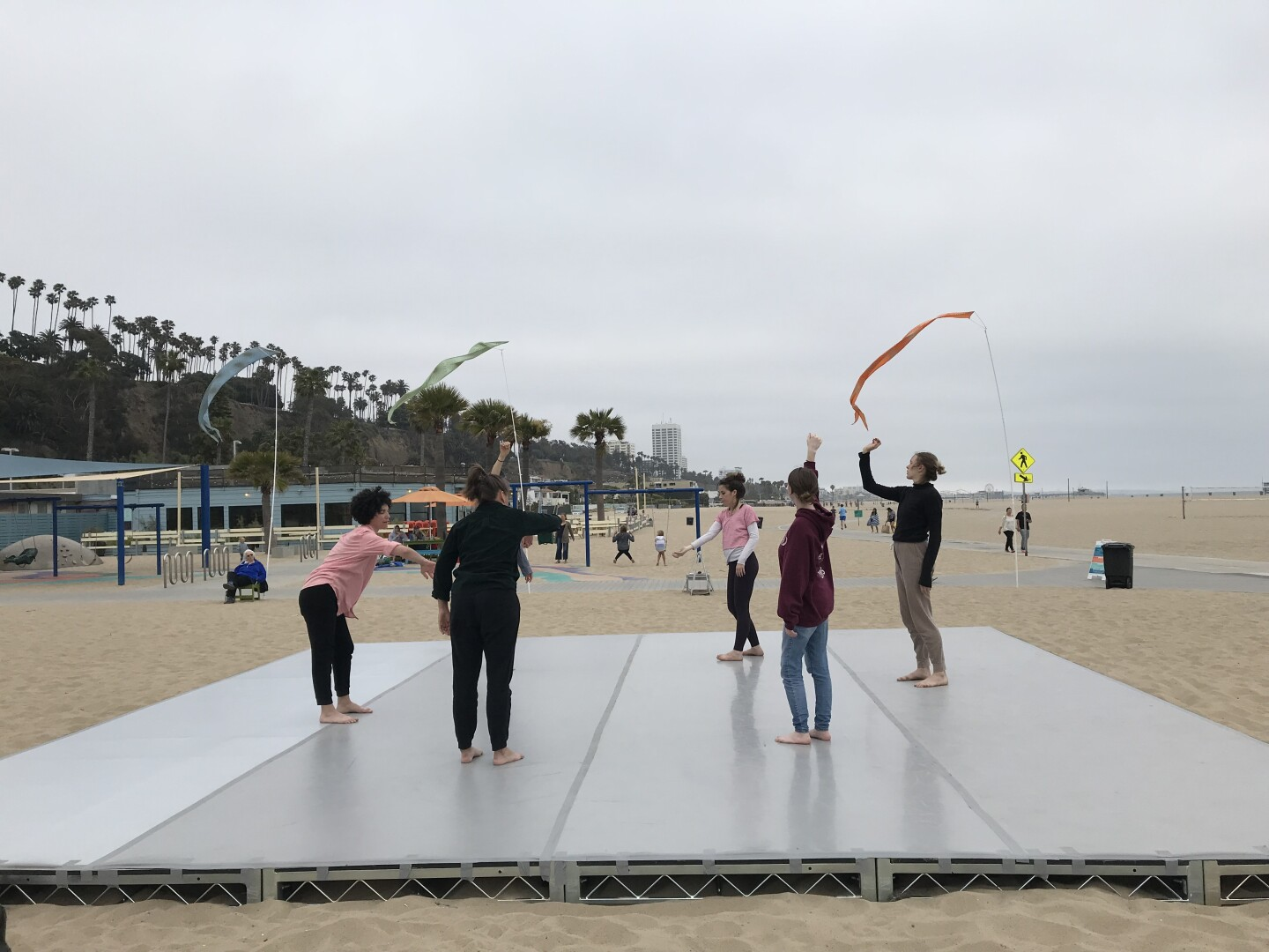 Participants stand on a platform placed on top of the sand at Santa Monica Beach. The participants are waving around different colored scarves in the air. The sky above them is overcast.