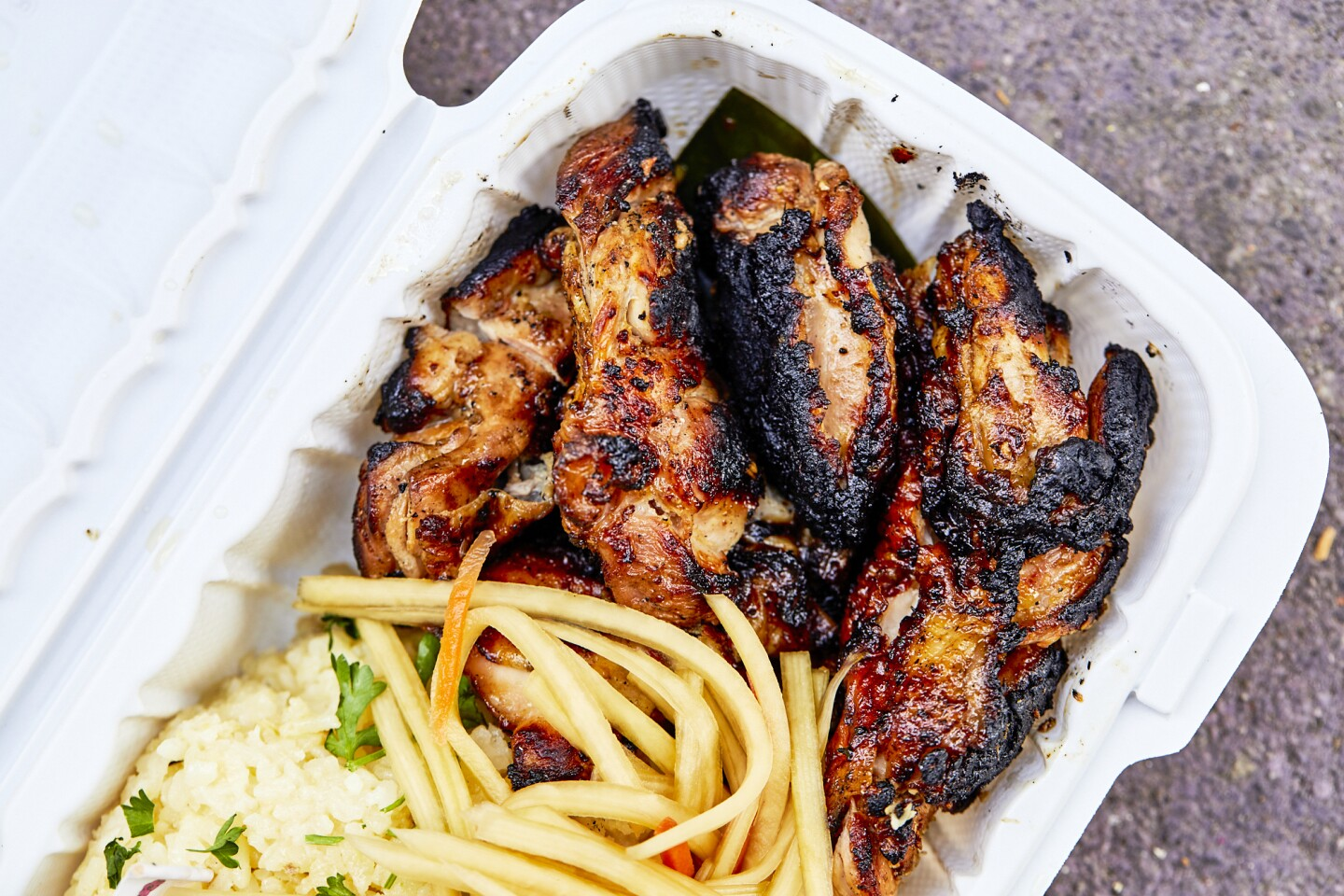 Chicken inasal, grilled chicken, from Mano Po over a bed of rice and packaged in a white to-go box.
