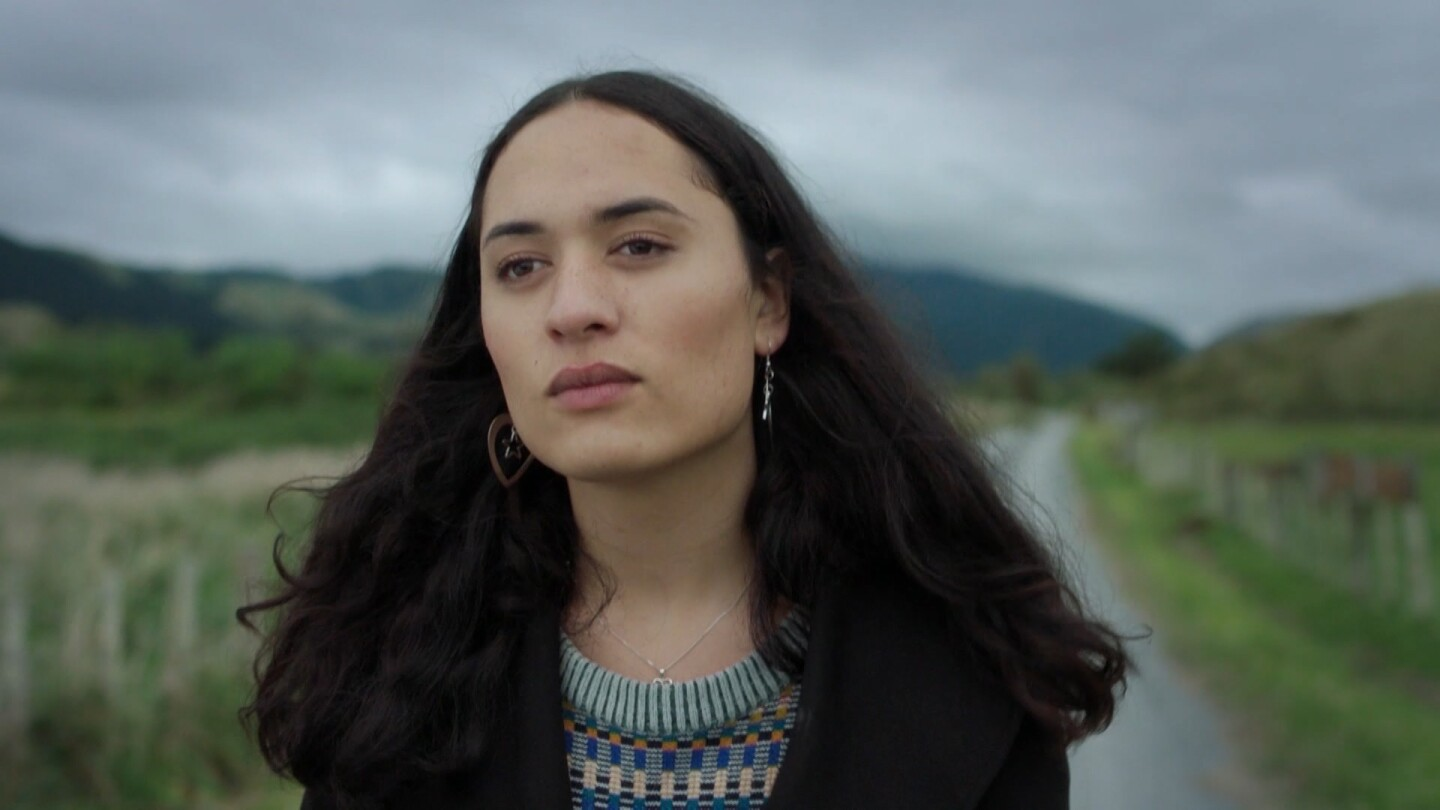 "Te Awarangi ""Awa"" Puna, a transgender Maori teen, walks along a dirt road seen behind her."