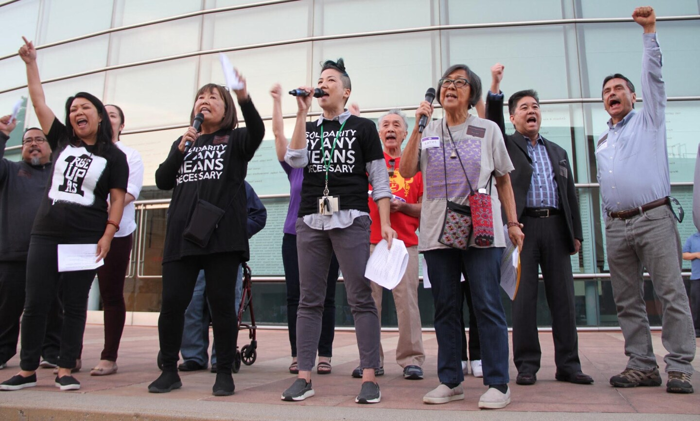 About ten people stand together speaking into microphones. Several raise their fists to the sky.