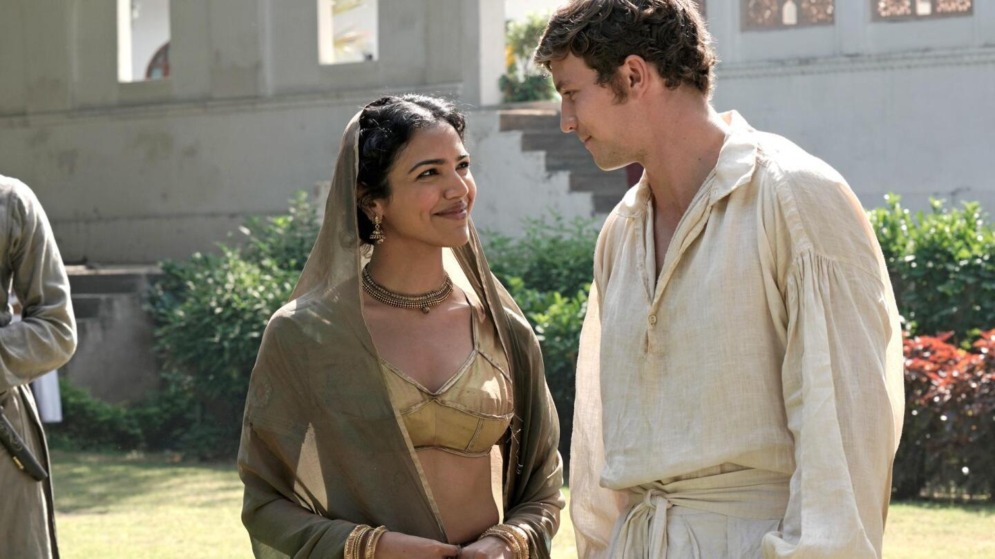 """Chanchal (Shriya Pilgaonkar) and Daniel Beecham (Leo Suter) smile at each other. 