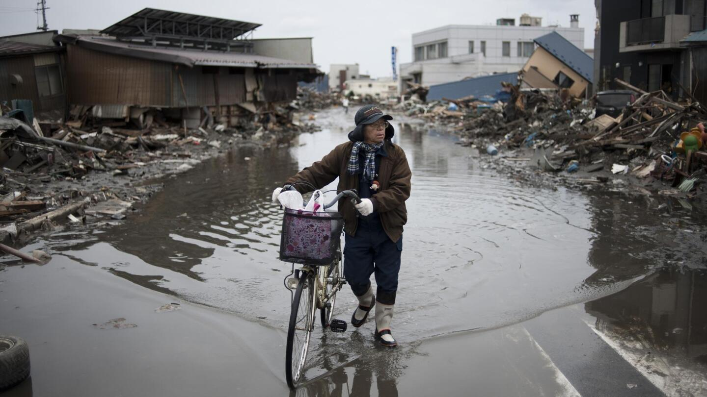 """A resident of a Japanese town pushes his bike through a flooded street lined with wreckage. 