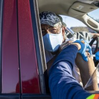 A wrinkled man in a face mask and cap gets a vaccine in his arm as he sits in his car.
