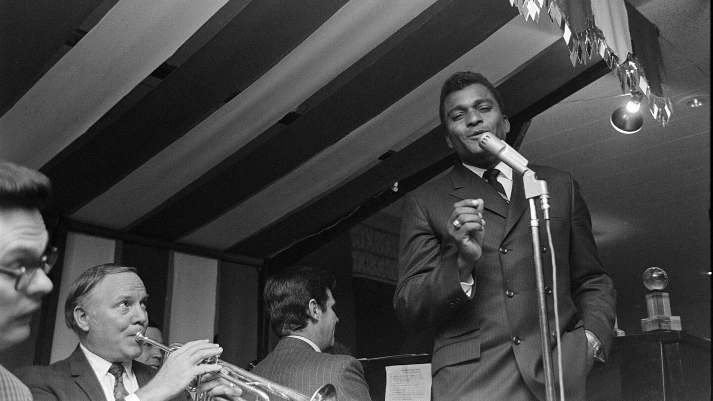 "Charley Pride sings into a microphone. | From ""Country Music: The Sons and Daughters of America (1964-1968)"""