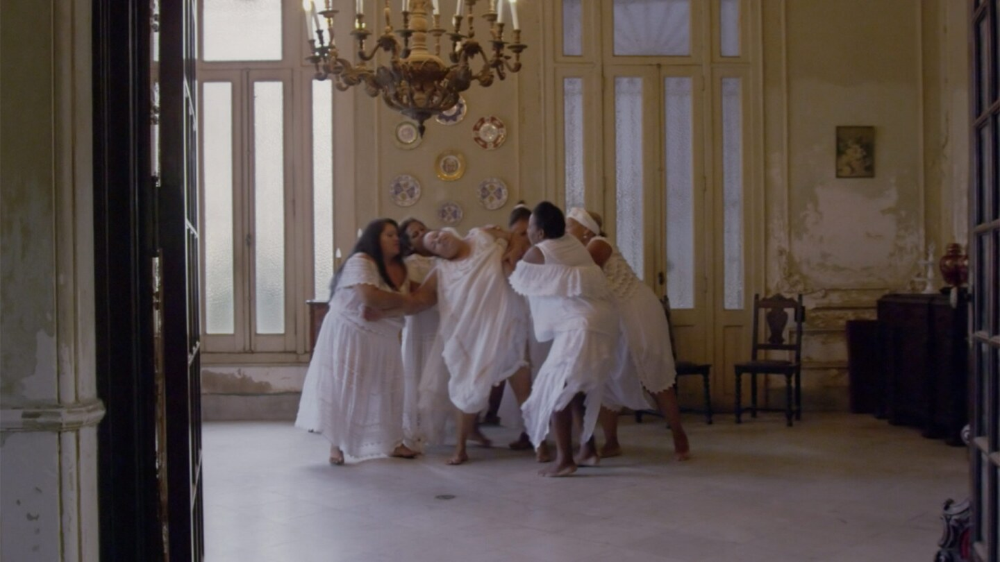 "Still from ""Triste, Louca ou Ma:"" 6 Women Huddle in a dance."