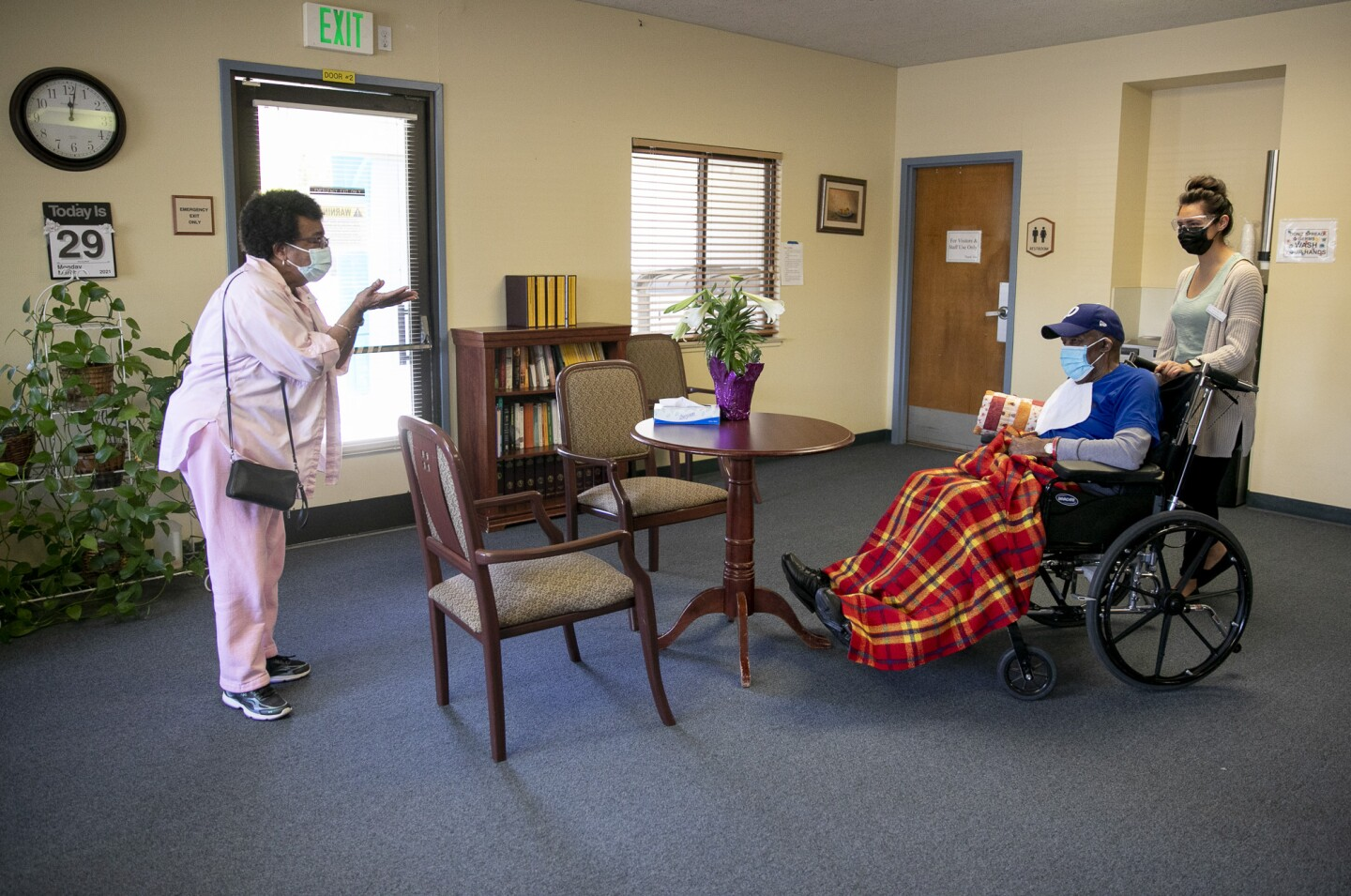 Ouida Dill, left, blows a kiss to her husband David at the end of their near-daily visit at Lincoln Glen Skilled Nursing Facility on March 29, 2021 in San Jose, California.