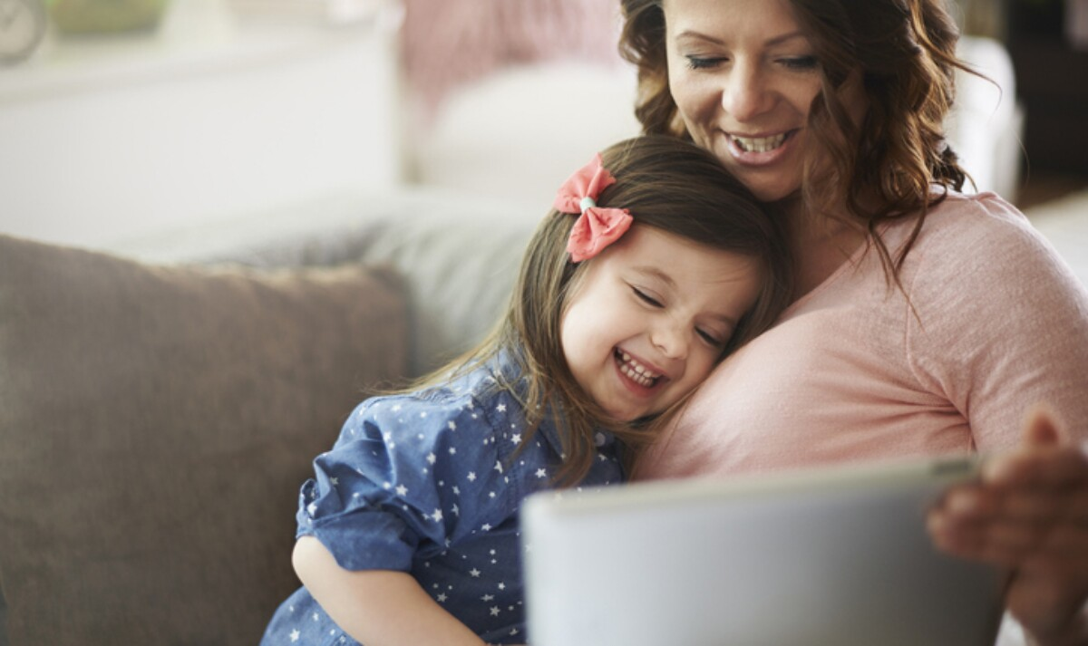 A woman and a little girl sit on a couch in front of a laptop.