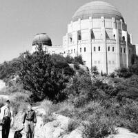 A few people trek down a road with the Griffith Observatory in the background.