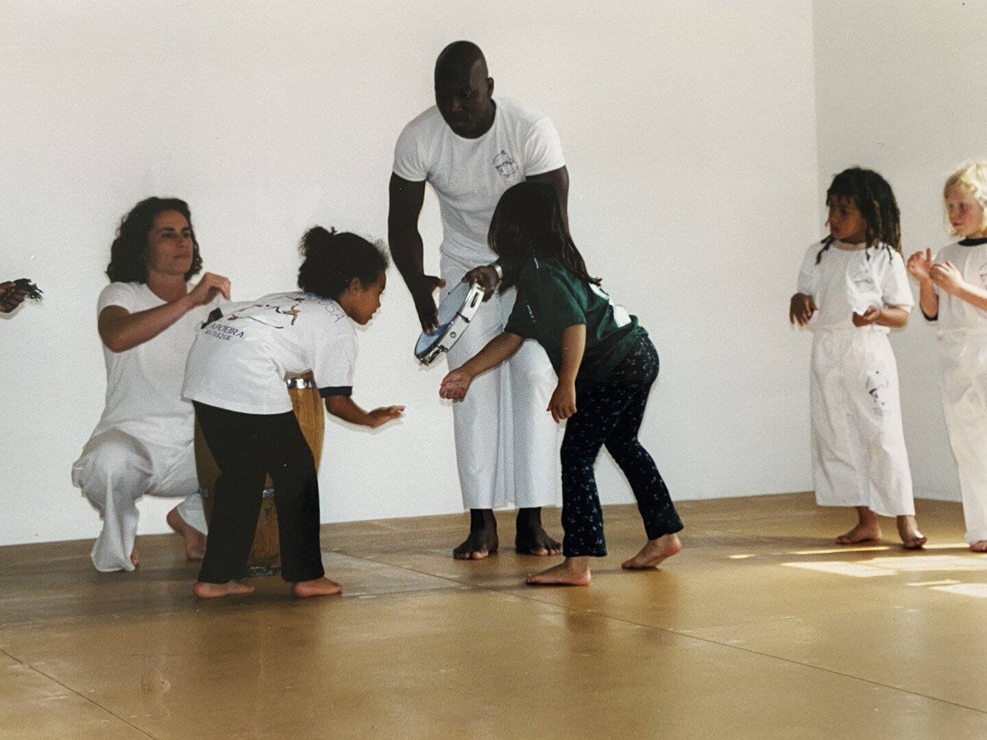 Lukaza and Kenja learn rituals of entering the capoeira roda with Author and Mestre Amen Santo at Brasil Brasil Cultural Center.
