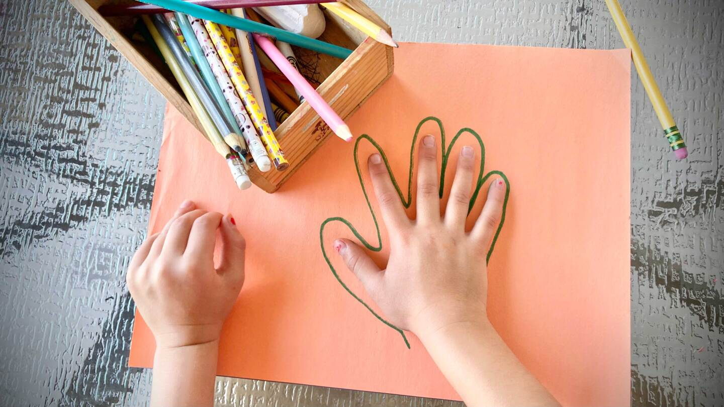 Chld tracing hand on orange construction paper.