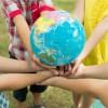 Cuatro niños sostienen un globo terráqueo.