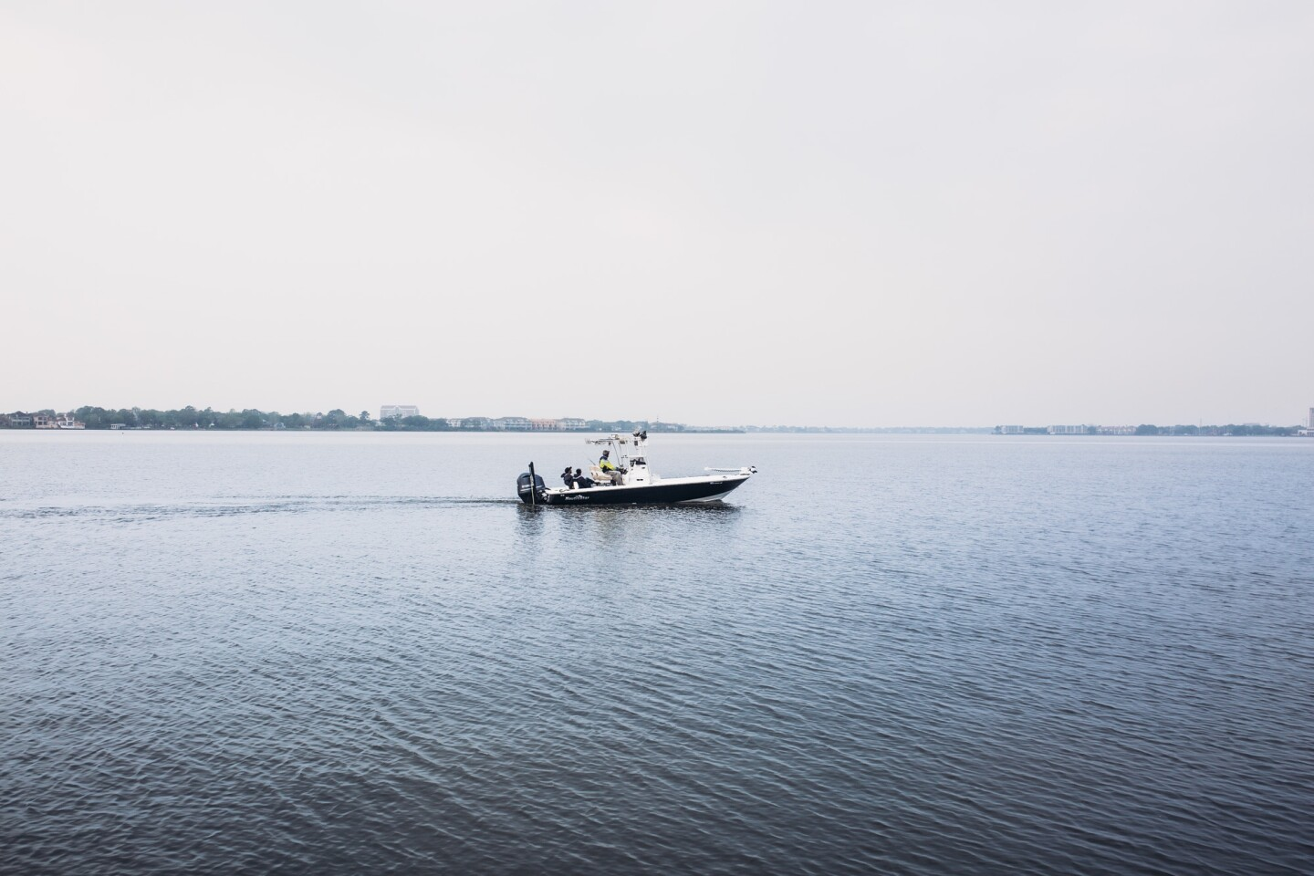 A fishing boat ventures out on a clear, dark blue water. The sky above is gloomy and gray.
