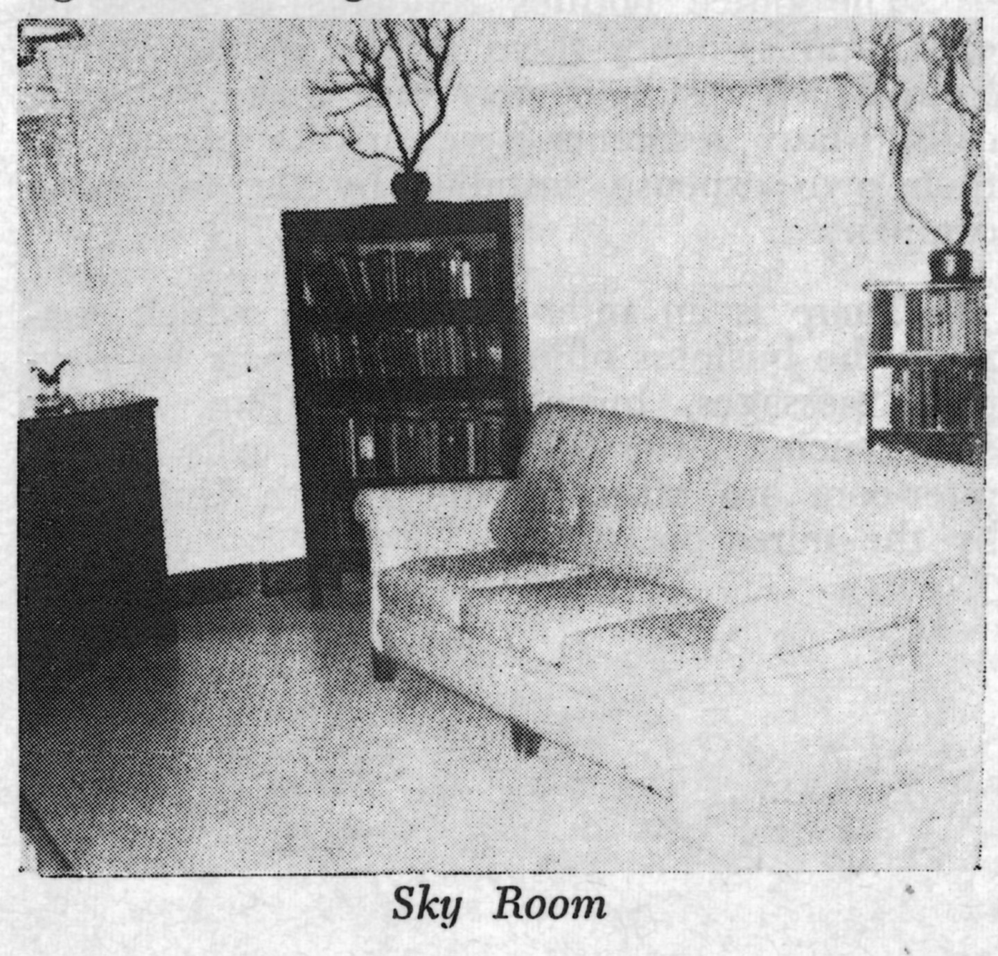 A black and white photo of a lounge at the Woman's Christian Temperance Union Home. There is a large couch and a bookshelf topped with a decorative tree.