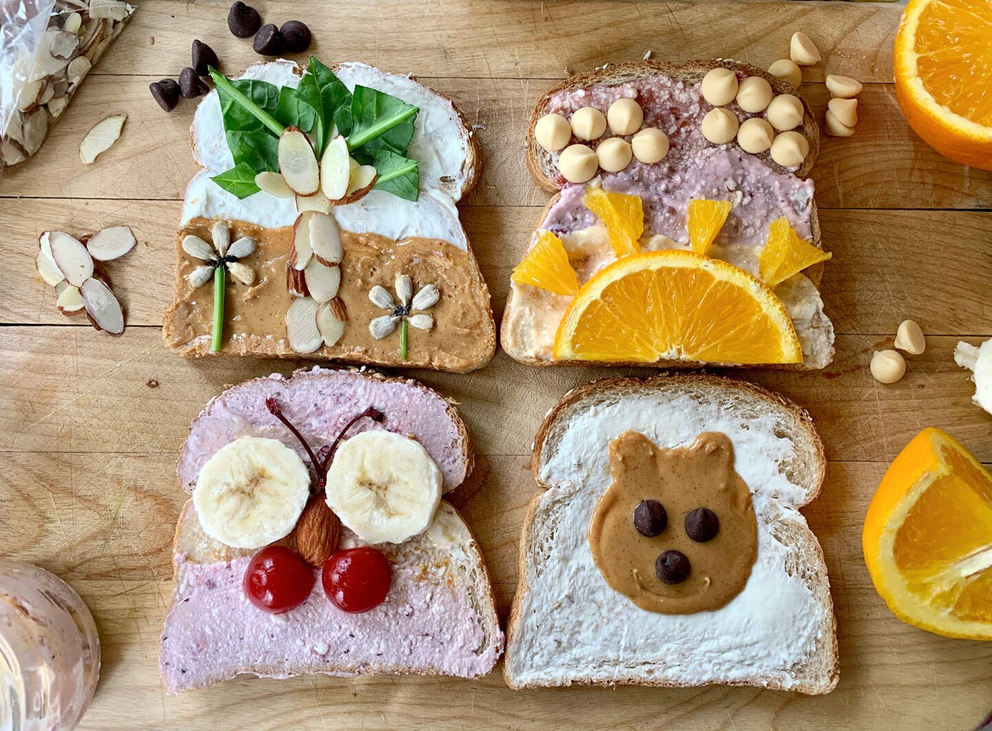 Four pieces of decorated toast featuring a palm tree, sunset, butterfly and teddy bear.
