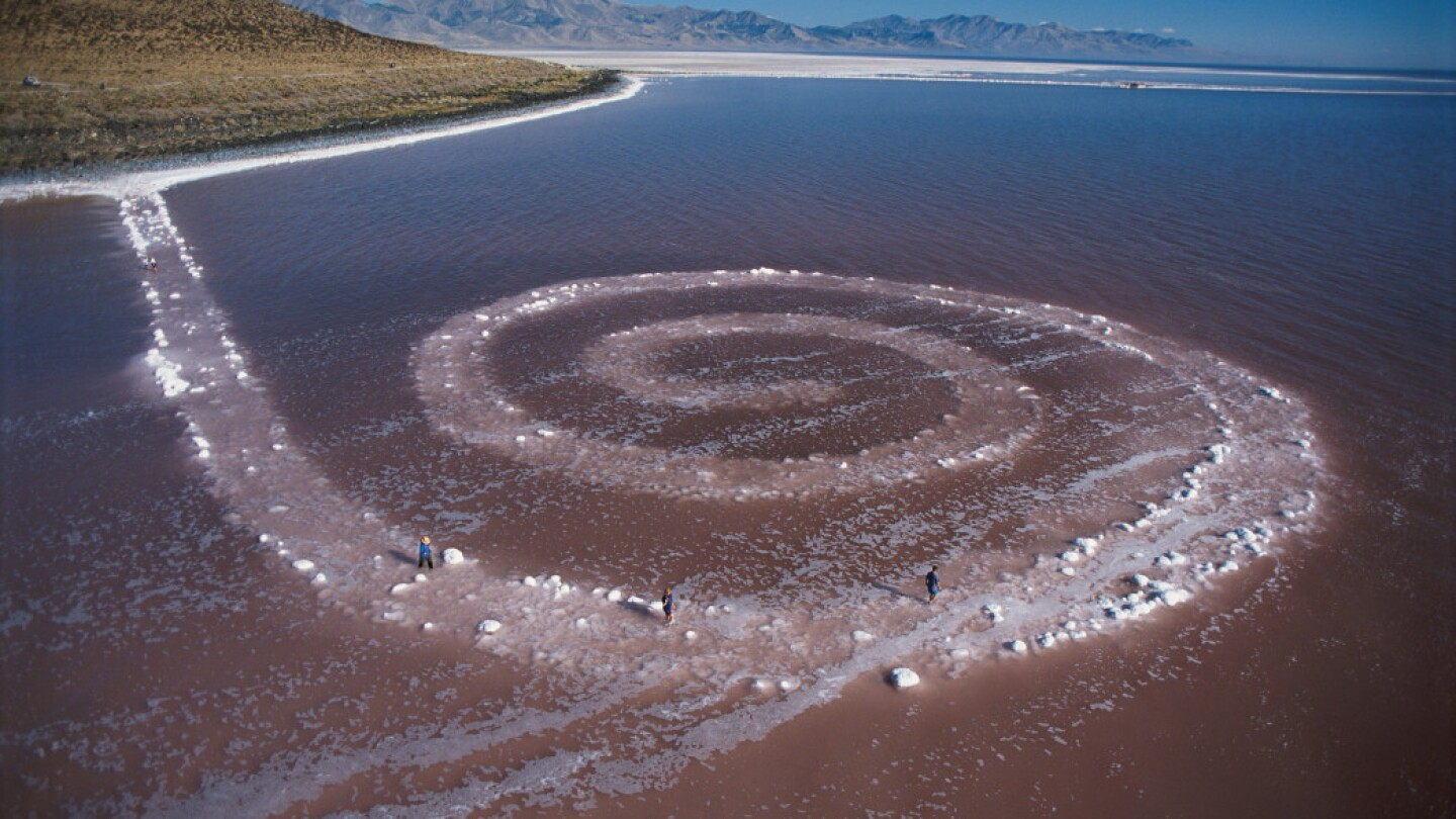 "A view of Robert Smithson's land art called ""Spiral Jetty"" made primarily of black basalt rocks and salt crystals."