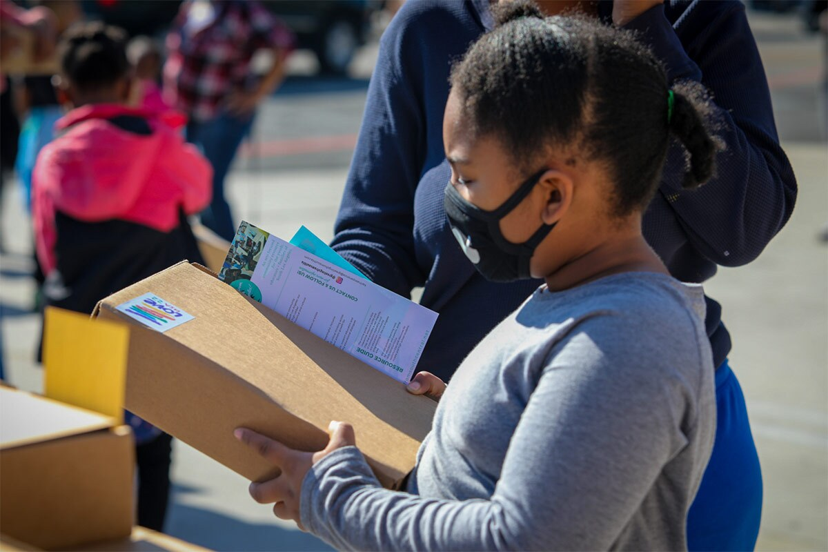 A small child wearing a mask receives a package from Greetings from South Central. | Tina Reeves
