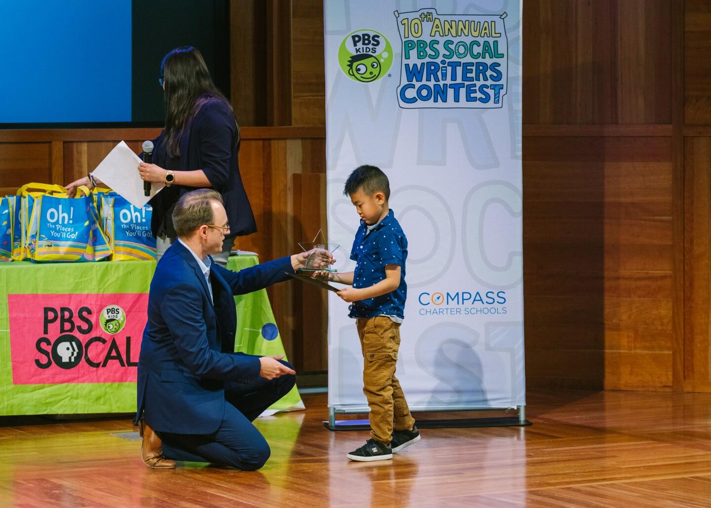 Education reporter Kyle Stokes awards first place to kindergartener Ezra Kim | Courtesy of Mae Koo Photography