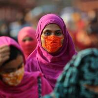 A garment worker wearing a protective mask returns from a workplace as factories reopened after the government has eased the restrictions amid concerns over the coronavirus disease (COVID-19) outbreak in Dhaka, Bangladesh, May 4, 2020. |REUTERS/Mohammad P