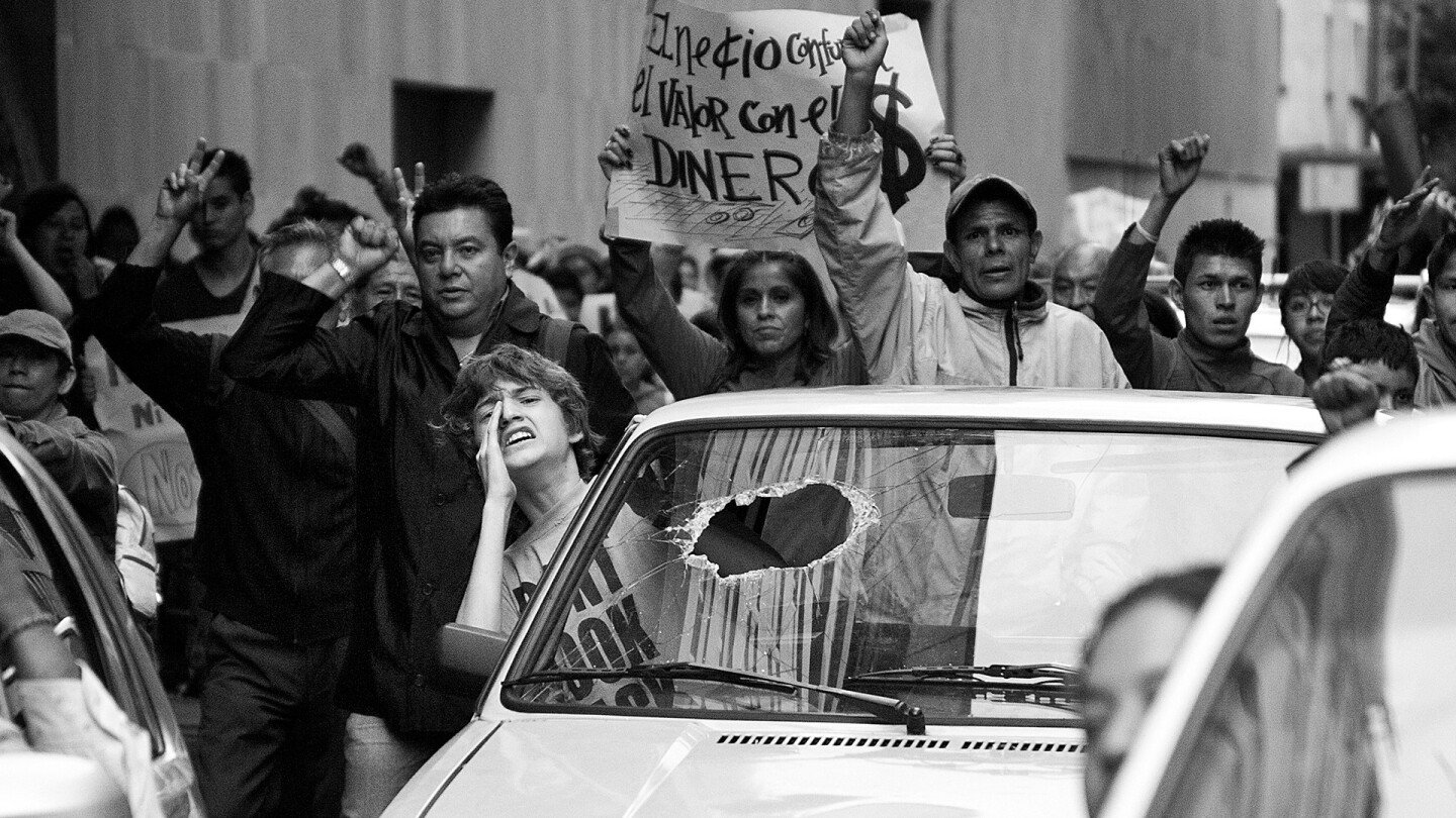 A boy sticks his upper body out a car window and yells out, with a crowd of demonstrators marching behind his vehicle.