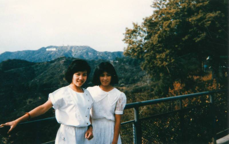 Two young women in white dresses pose in Griffith Park, with the Hollywood sign visible behind them.