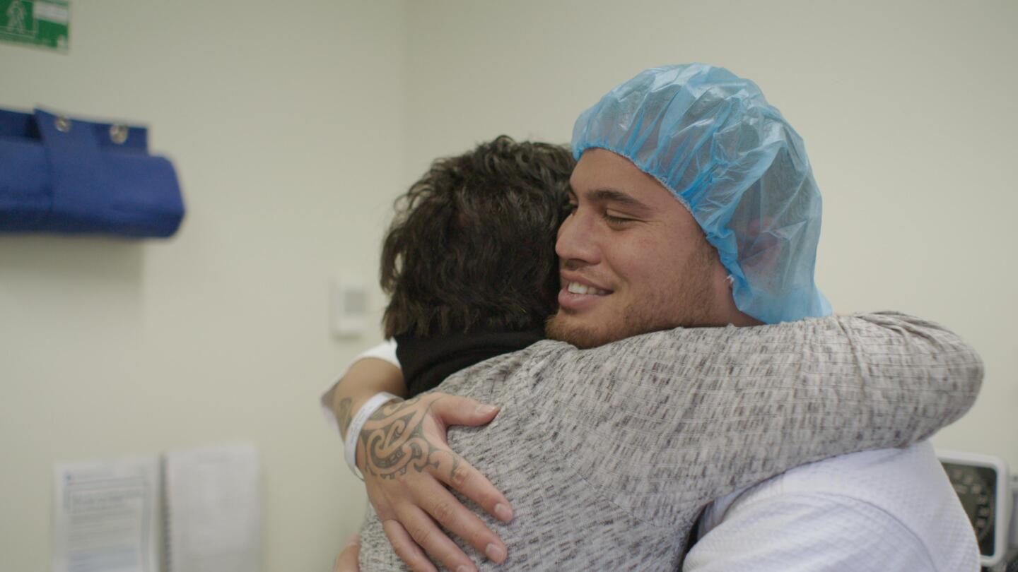 Stan Walker embraces another person.