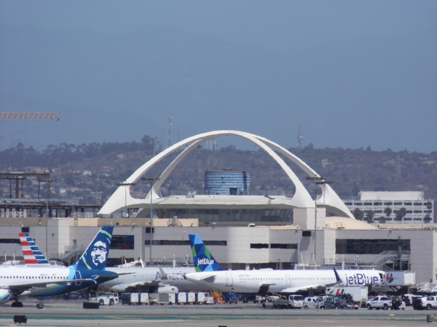 A view of LAX airport with planes docked in the runway.