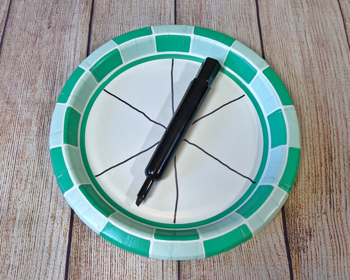 A paper plate is divided into six slices with a black marker.