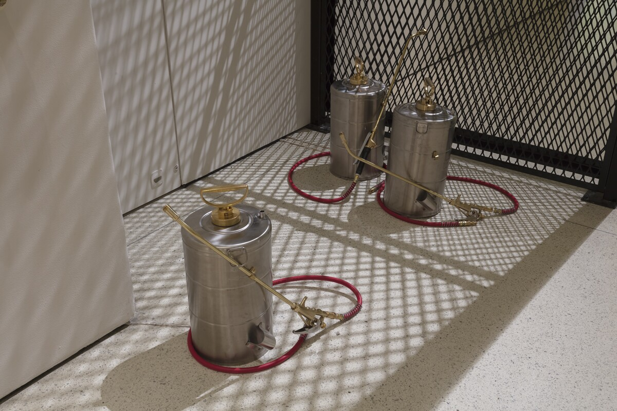 Three stainless steel insecticide sprayers with brass fittings sit on the floor. A mesh metal room divider casts diamond-shaped shadows over the cannisters.