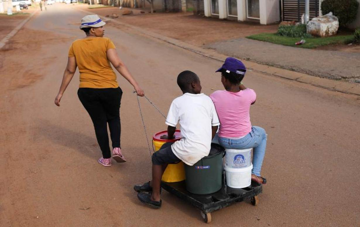Children sit on a trolley with buckets as the mother pulls it on their way to collect water from a nearby church, as their community experiences water cuts during a nationwide lockdown for 21 days to try to contain the coronavirus disease (COVID-19)