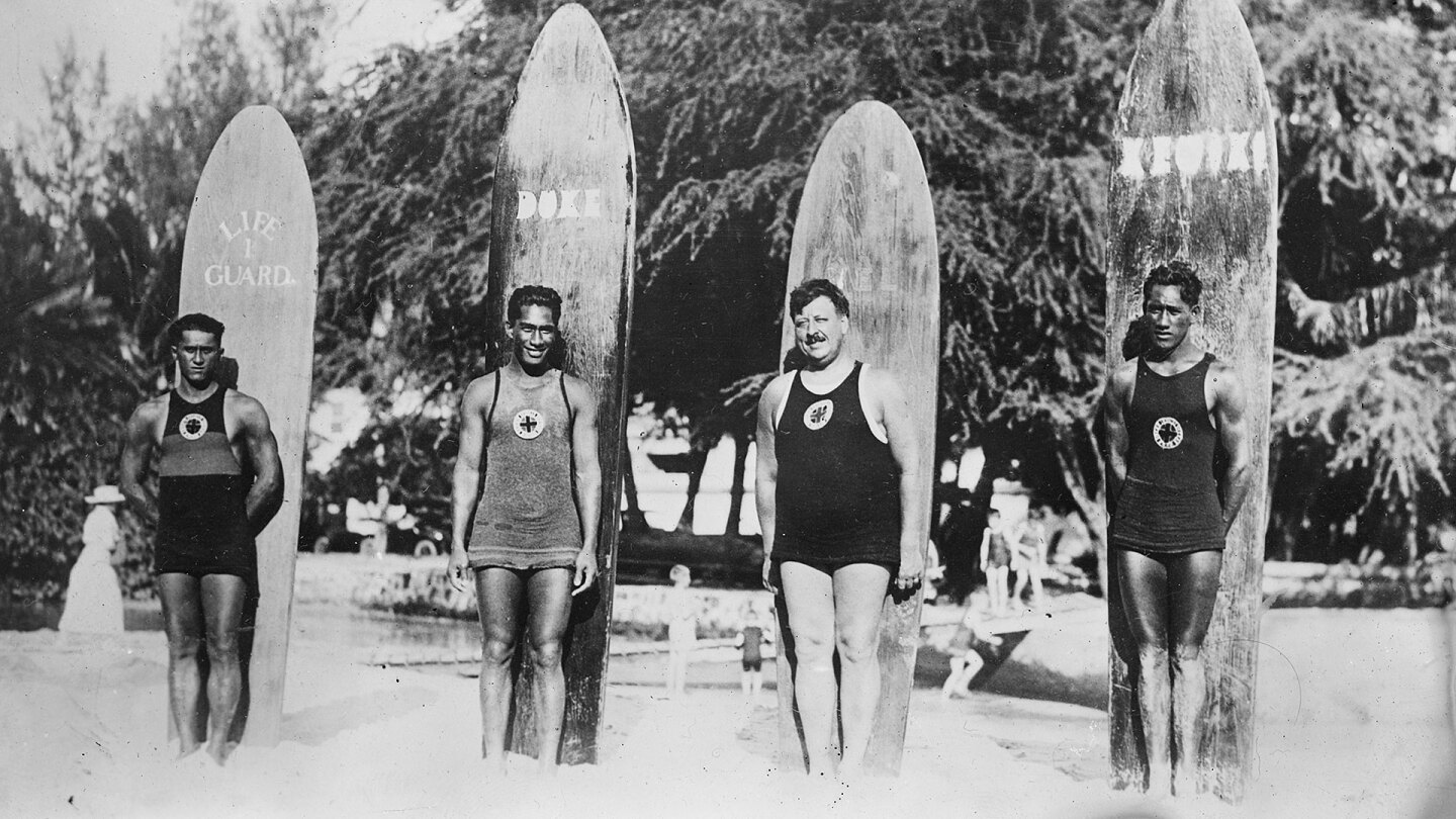 Four surfers stand in front of their boards- black and white