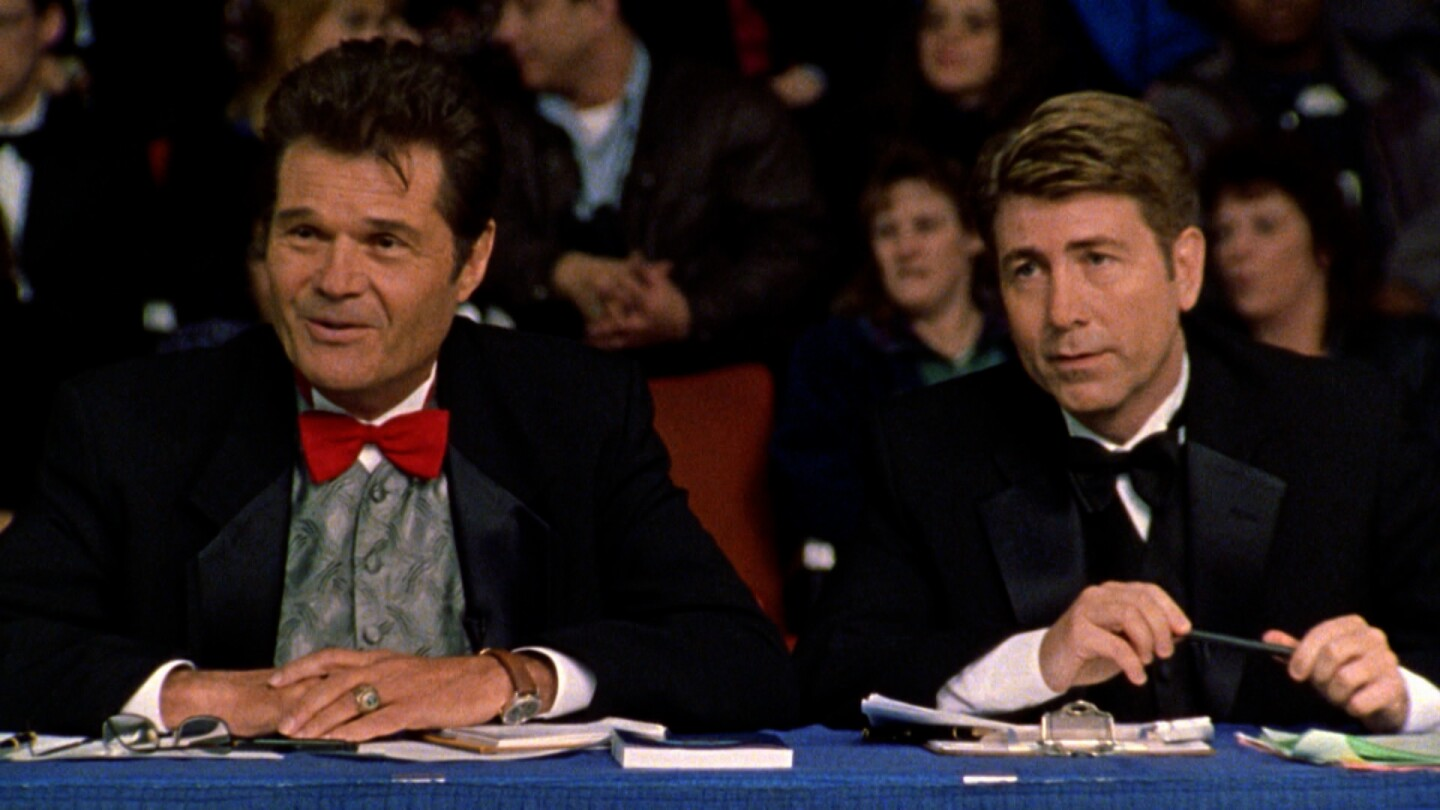 "Two dog show judges in the film ""Best In Show."""