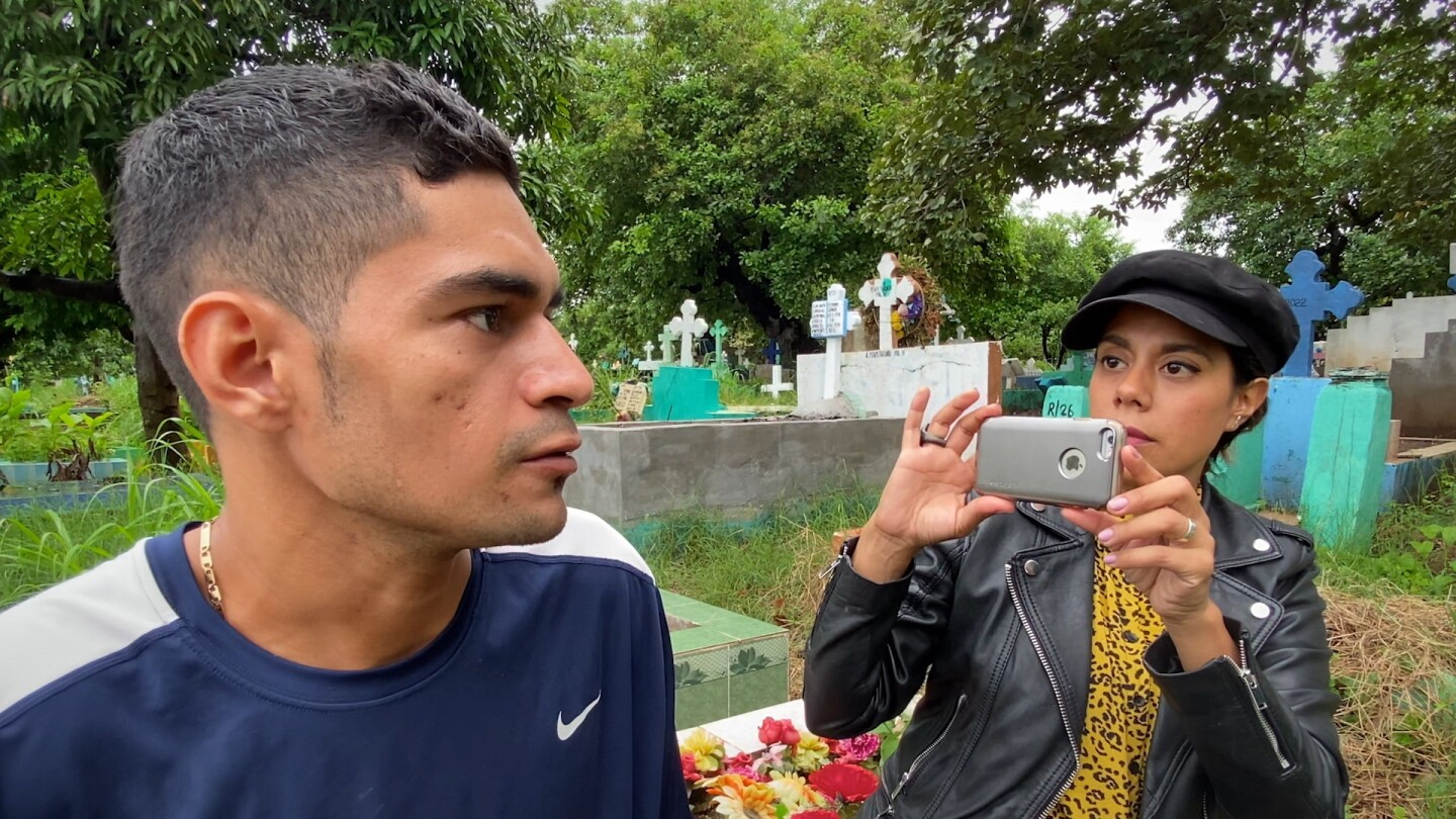 Filmmaker Adriana Trujillo (right) photographs Victor as the graveyard where he works in El Salvador.