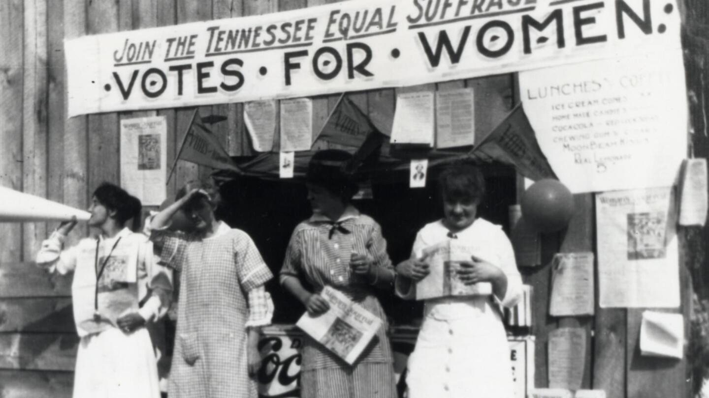 "Four women stand in front of a booth advocating for women's suffrage. | ""By One Vote: Woman Suffrage in the South"""