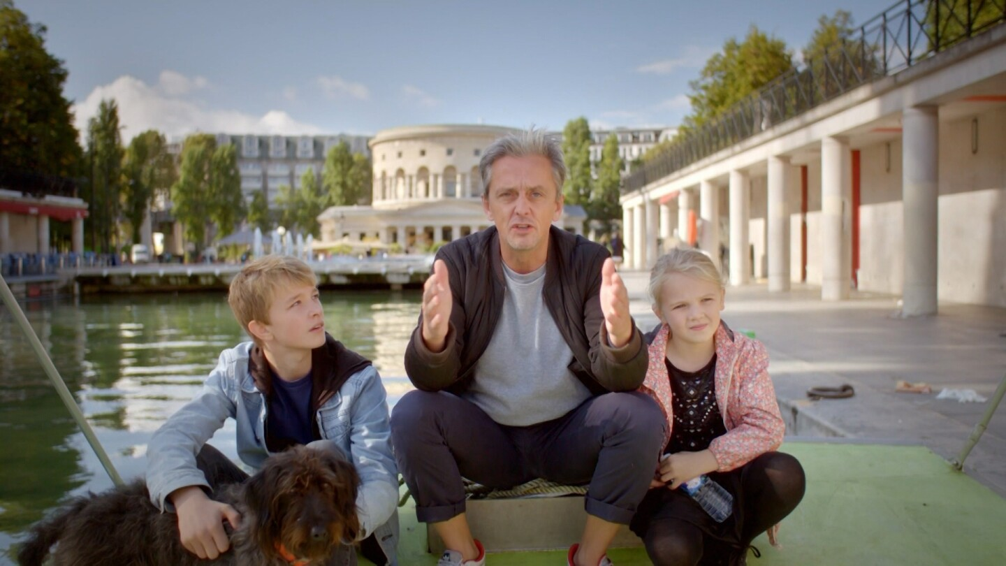 """Life-Sized City"" host Mikael Colville-Andersen sits beside a body of water in Paris with two children and a dog."