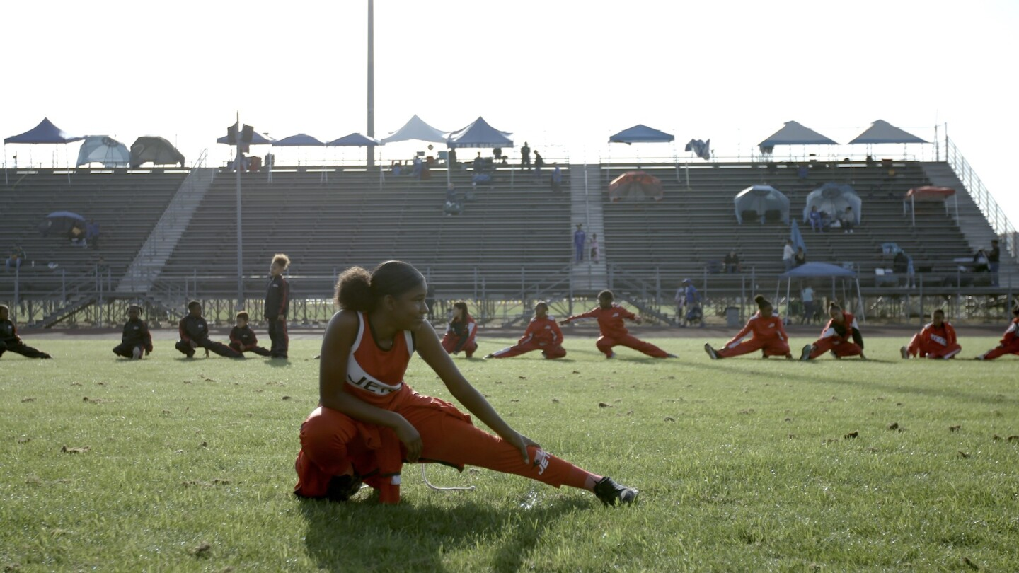 "Girl in foreground stretching, with teammates stretching behind her | Still from ""Born to Run"", SoCal Connected"