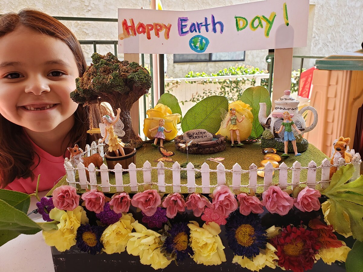 A smiling little girl poses with her Earth Day themed float made for the virtual Rosebud Parade.