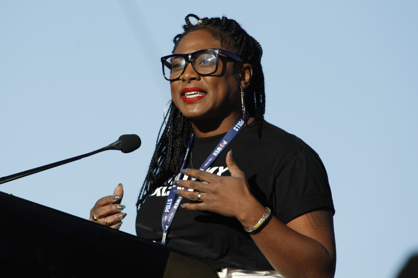 A woman with braided hair, red lipstick and thick, black sunglasses speaks at a podium.