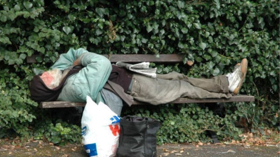 Homeless man sleeping on a bench | photo Voice of OC