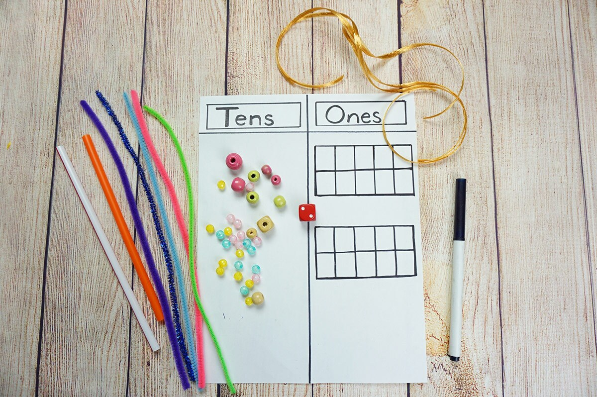 """A sheet of paper divided in two columns with the headings """"tens"""" and """"ones"""" with beads, pipe cleaners, pieces of string and a marker on top of it."""