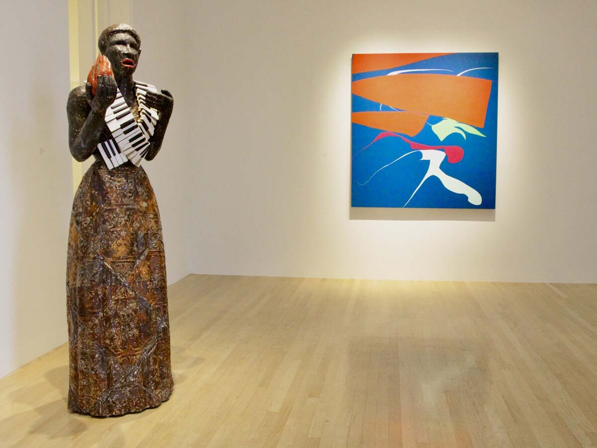 "Alison Saar's ""Torch Song,"" 2020 in wood, copper, ceiling tin, enamel paint, leather belts and vintage piano keys (72 x 22 x 26) next to Heather Gwen Martin's ""Touch"" from 2020. Oil on linen, 60 x 56 in. 