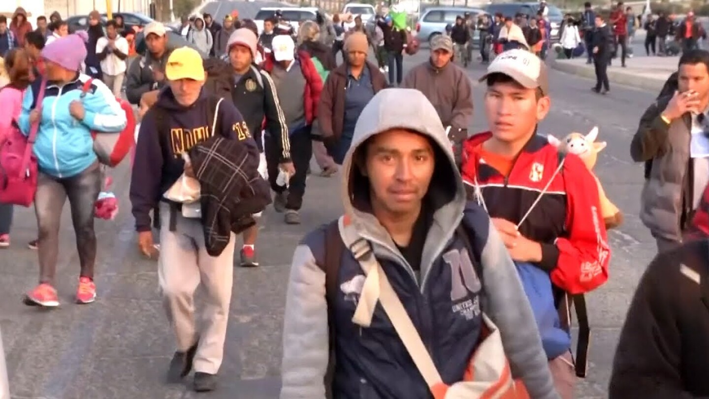 """Still from footage of coverage of the migrant caravan. 