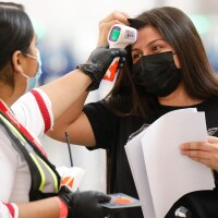 A Passenger Service Representative for Avianca Airlines in the Tom Bradley International Terminal at LAX takes the temperature of Cindy Perla on Nov. 16, 2020 in Los Angeles. | Al Seib / Los Angeles Times