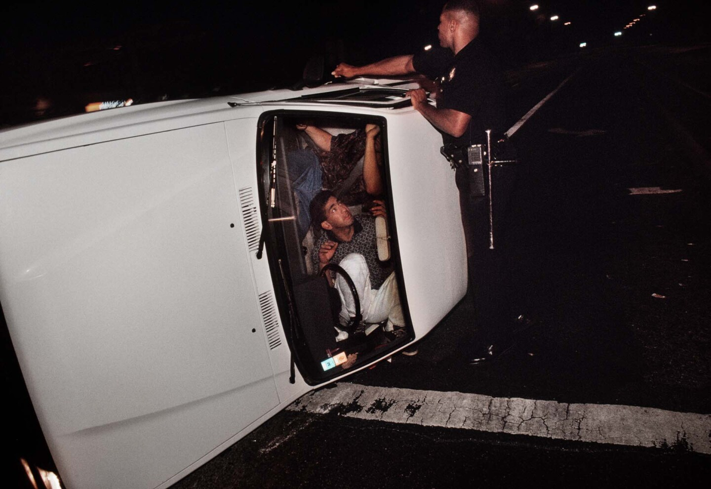 Pacific Division Officer Hoskins tries to pry open the door of a truck involved in a accident that left the driver and passenger locked in the overturned vehicle. | Joseph Rodriguez