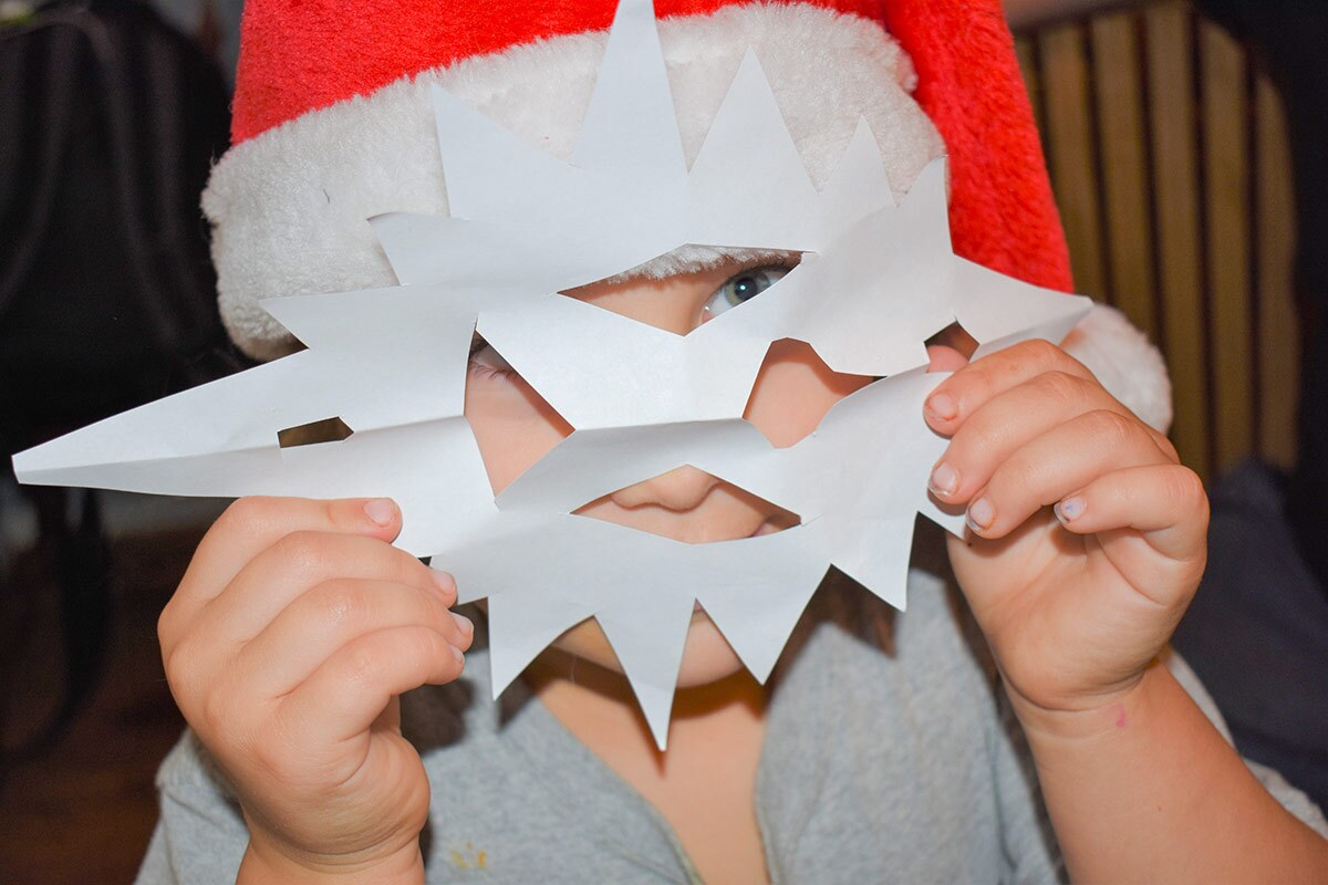 A small child wearing a red Santa hat holds a paper snowflake in front of the face like a mask.